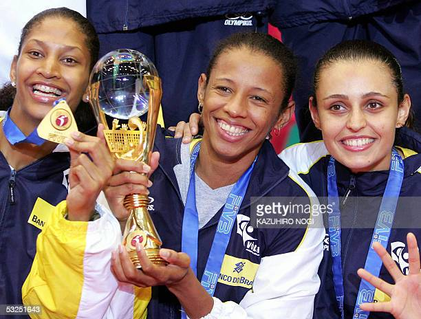 Brazilian volleyball team captain Valeska Menezes holds the champion's trophy with her teammates Kaita Rodrigues and Marcelle Moraes during the...