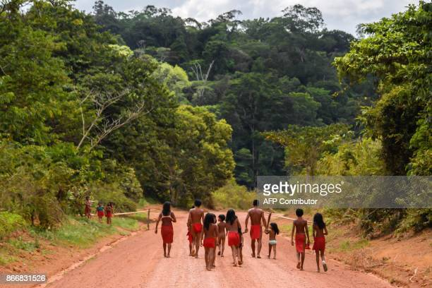 Brazilian Waiapi walk on the road of the Waiapi indigenous reserve, at Pinoty village in Amapa state in Brazil on October 12, 2017. The Waiapi are...