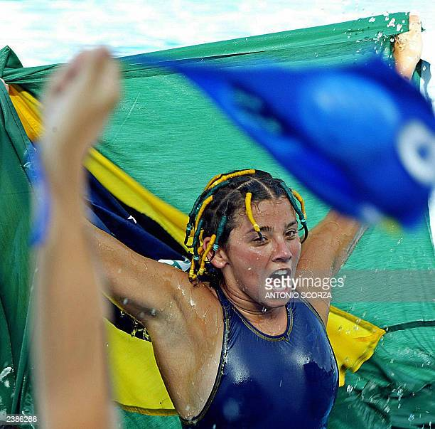 Brazilian water polo player Flavia Fernadez waves the Brazilian flag celebrating their victory over Cuba by 6/5 to win the bronze medal on the XIV...