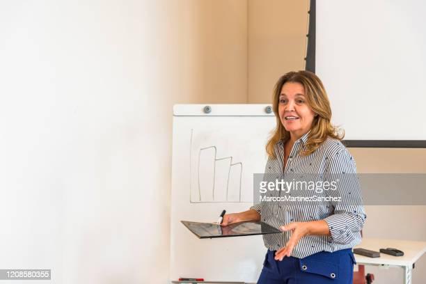 donna brasiliana che fa presentazione di contenuti in sala riunioni - maestra foto e immagini stock