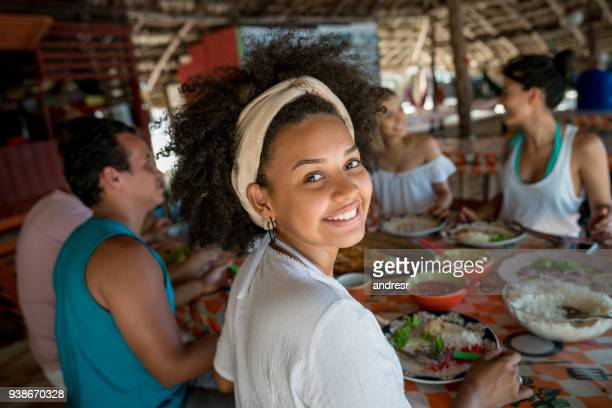 Brazilian woman eating with friends at a beach restaurant