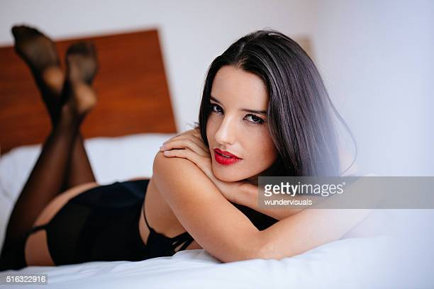 brazilian woman in sexy lingerie lies in bed - suspenders stock photos and pictures