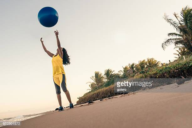 brazilian woman in yellow shirt throwing gymnastic in the air