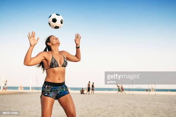 リオ ・ デ ・ ジャネイロのビーチでの頭の上のボールをジャグリングするブラジルの女性 - ビーチサッカー ストックフォトと画像
