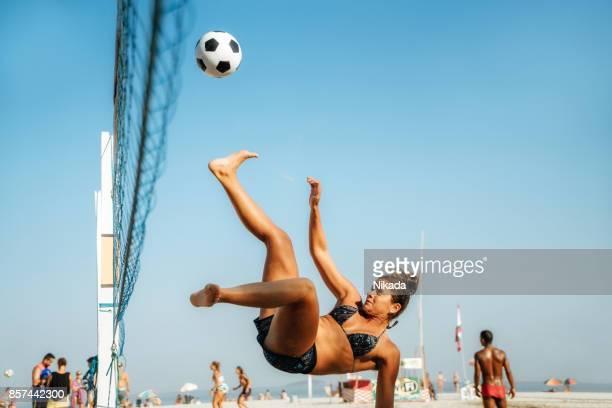 brasilianische frau springen und treten kugel am strand in brasilien - strandvolleyball spielerin stock-fotos und bilder
