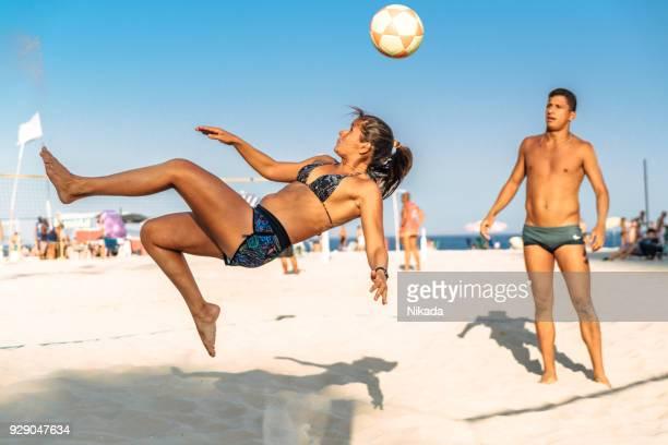 brazilian woman jumping and kicking ball on beach in brazil - beach volley foto e immagini stock