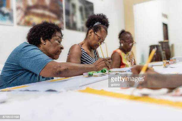 brazilian woman painting textiles in tailor work room of social project - art and craft product stock pictures, royalty-free photos & images