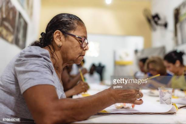 brazilian woman painting textiles in work room of social project