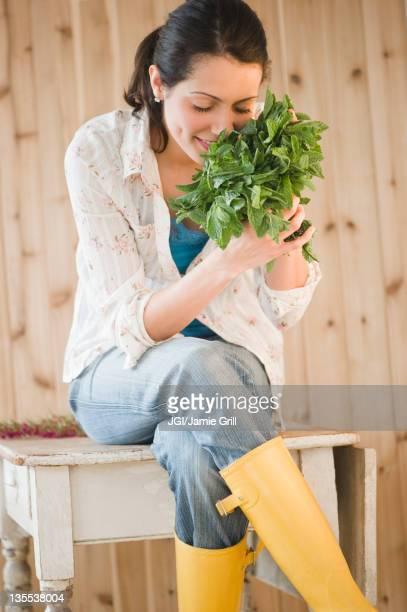 Brazilian woman smelling fresh mint