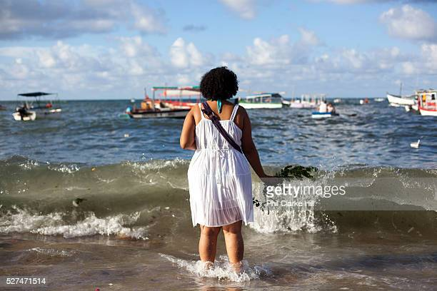 Brazilian woman standing by the sea in contemplation and prayer making offerings of flowers to Yemanja the Orixa goddess of the Sea and waterFebruary...