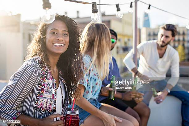 brazilian woman with friends at rooftop party - brazilian men stock photos and pictures