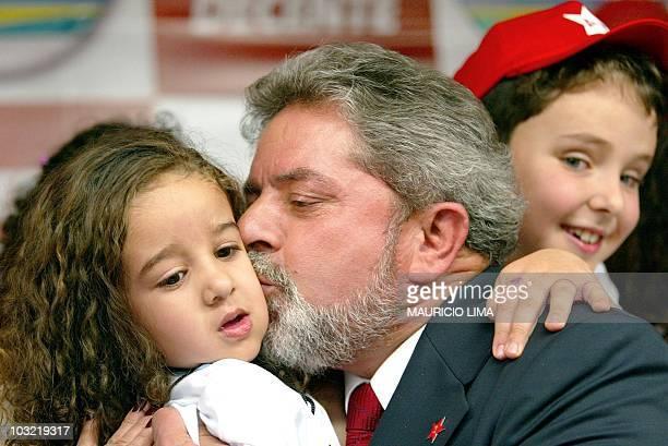 Brazilian Workers' Party Presidential candidate Luis Inacio Lula da Silva kisses a girl 19 September after signing the project Presidente amigo de...
