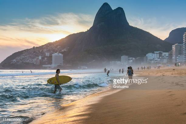 brazilian young man walking on ipanema beach with surfboard - copacabana beach stock pictures, royalty-free photos & images