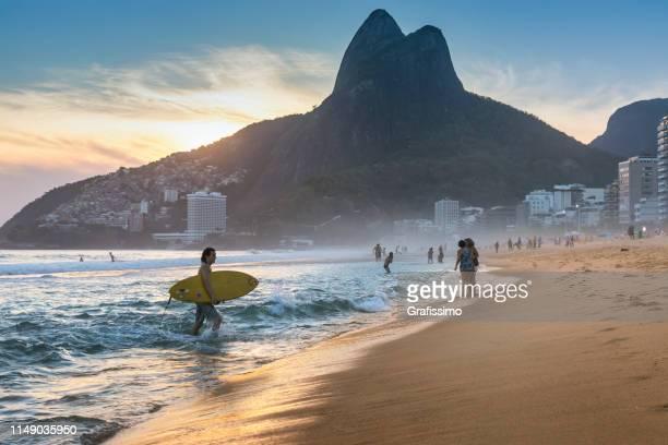 brasilianischer junger mann spazierten mit surfbrett am strand von ipanema - copacabana rio de janeiro stock-fotos und bilder