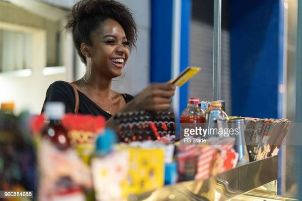 brazilian young woman buying some street products - happy merchant stock pictures, royalty-free photos & images