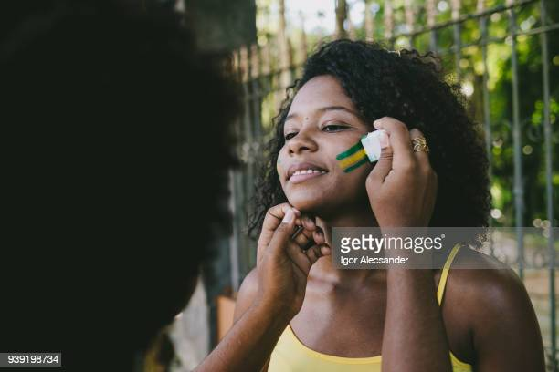 Brazilian young woman fan making up with the colors of Brazil
