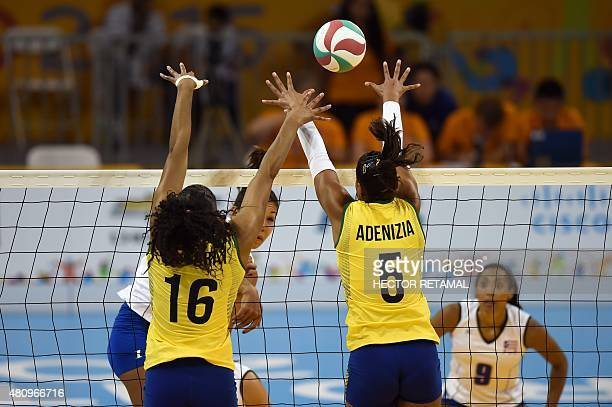 Brazilian's Fernanda Rodriguez and Adenizia Da Silva vie for the ball with Karina Ocasio of Puerto Rico during the Volleyball Women Preliminary at...