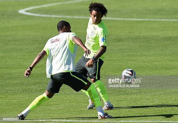 Brazilians Marcelo and Fernando vie for the ball during a training session of the Brazilian national football team at the squad's Granja Comary...