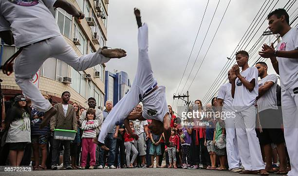 Brazilians perform capoeira a Brazilian martial art mixing dance and music ahead of the arrival of the Olympic torch relay in Rio's North Zone on...