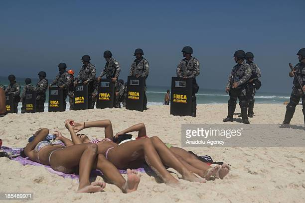 Brazilians sunbathe near the National Guard officers at the Barra da Tijuca beach before the auction of the Libra oil field Brazil's largest single...