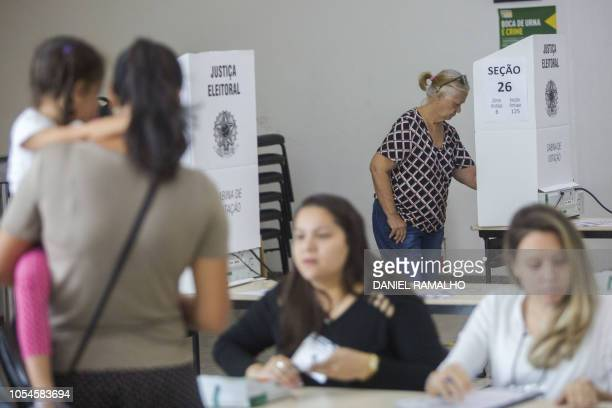 Brazilians vote at a polling station during the second round of the presidential elections in Rio de Janeiro on October 28 2018 Brazilians will...