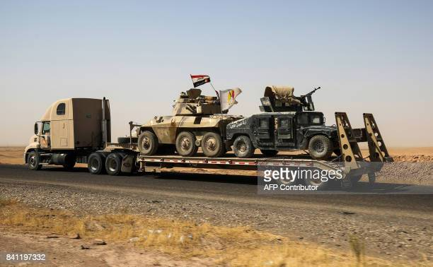 Brazillian-made EE-9 Cascavel armoured vehicle and a US-made Humvee, belonging to the Hashed al-Shaabi paramilitaries, are seen towed on a trailer...
