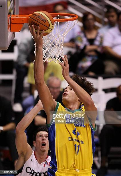 Brazil's Anderson Varejao drives a dunk against Canada's Andy Rautins during a FIBA Americas Championship semifinals basketball game in San Juan...