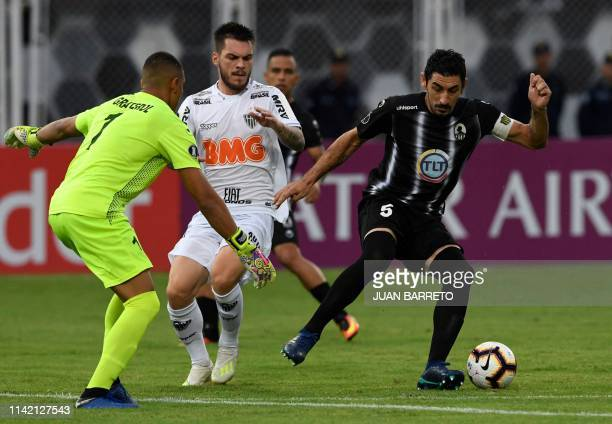 Brazil's Atletico Mineiro player Luan Paiva vies for the ball with Venezuela's Zamora goalkeeper Joel David Graterol during the Copa Libertadores...