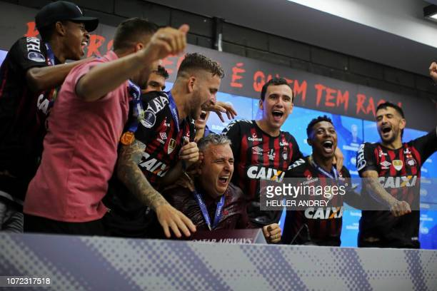 Brazil's Atletico Paranaense coach Tiago Nunes and players celebrate after he was poured water during press conference after winning the 2018 Copa...