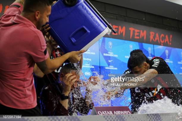 TOPSHOT Brazil's Atletico Paranaense coach Tiago Nunes gets water thrown by Luis Gonzalez and other players during press conference after winning the...