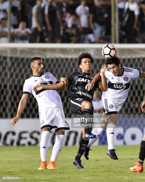 Brazil's Botafogo player Camilo vies for the ball with Paraguay's Olimpia players Hernan Pellerano and Cristian Riveros during their Copa...