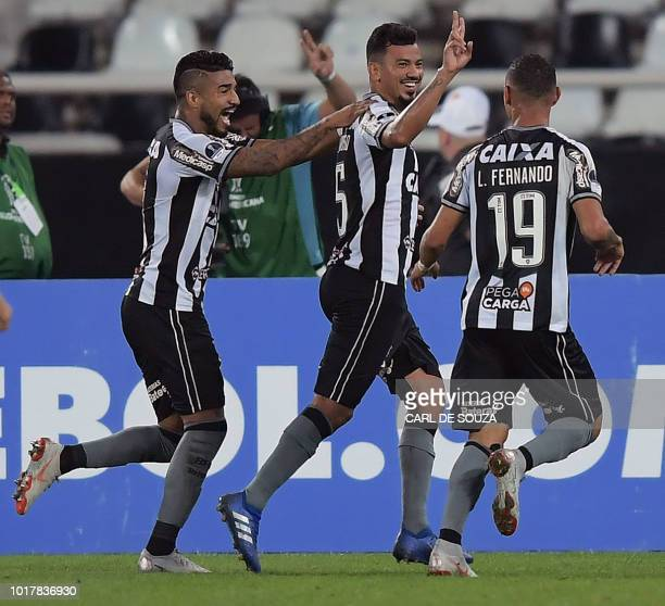 Brazil's Botafogo player Rodrigo Lindoso celebrates with team mates Luiz Fernando and Aguirre after scoring against Paraguay's Nacional during their...