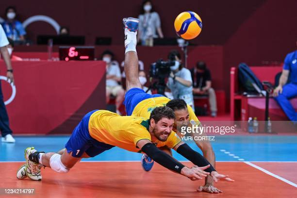 Brazil's Bruno Rezende and Mauricio de Souza dive for the ball in the men's preliminary round pool B volleyball match between Brazil and Argentina...