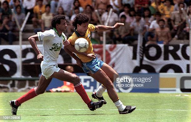Brazil's Careca charges the ball as Algeria's Lakhdar Belloumi tries for a block 06 June 1986 at Jalisco Stadium in Guadalajara in the second period...