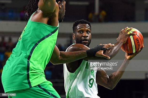 Brazil's centre Nene Hilario holds off Nigeria's shooting guard Chamberlain Oguchi during a Men's round Group B basketball match between Nigeria and...