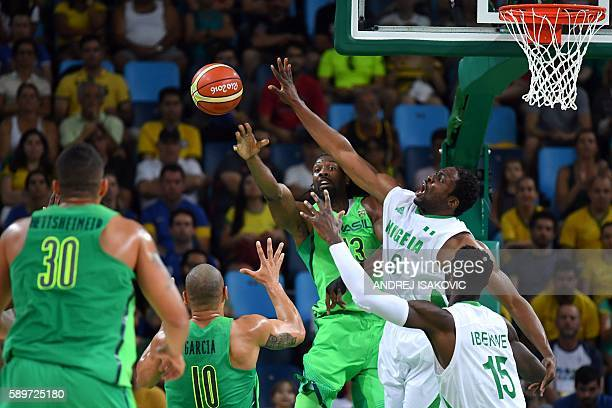 Brazil's centre Nene Hilario pass under pressure from Nigeria's power forward Ike Diogu during a Men's round Group B basketball match between Nigeria...