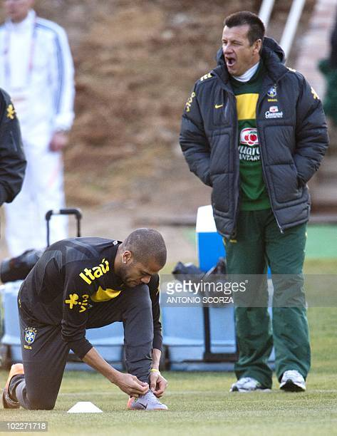 Brazil's coach Dunga watches as forward Daniel Alves readies for training on June 21 2010 at the Saint Sthithians School in Johannesburg Brazil faces...