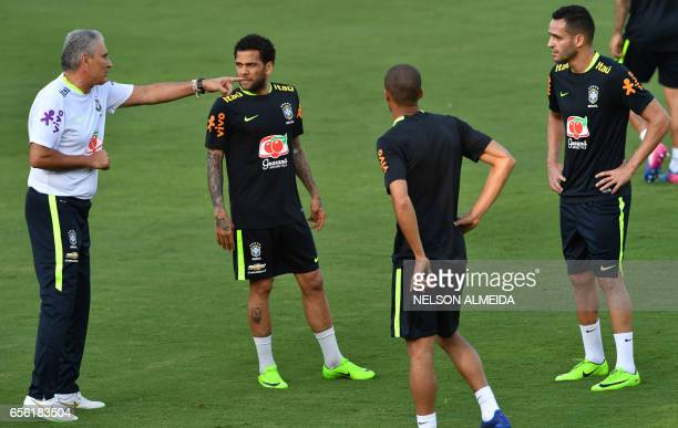 Brazil's coach Tite gives instructions to footballers Daniel Alves Miranda and Renato Augusto during a training session at the Corinthians team...