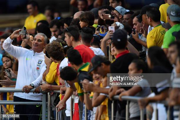 Brazil's coach Tite poses with fans after a training session at the Morumbi stadium in Sao Paulo Brazil on March 25 2017 ahead of a 2018 FIFA World...