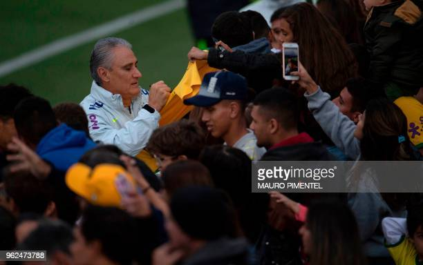 Brazil's coach Tite signs autographs to supporters after a training session of the national football team ahead of the FIFA 2018 World Cup at Granja...
