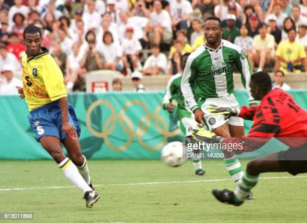 Brazil's Conceicao Flaviol scores a goal against Nigeria's Alozie Uche and goalkeeper Hyacinth Babayaro 31 July during the Olympic soccer semifinal...