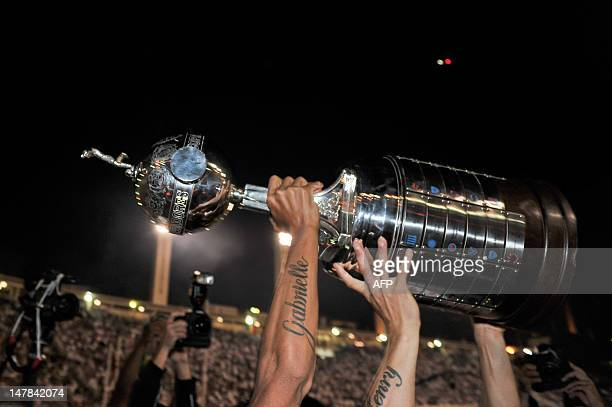 Brazil's Corinthians players hold up the Copa Libertadores trophy after their victory against Argentina's Boca Juniors during their Copa Libertadores...