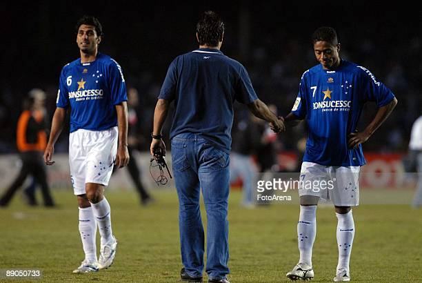 Brazil's Cruzeiro head coach Adilson Batista reacts with team mate Marquinhos after loosing their final match against Argentina's Estudiantes during...