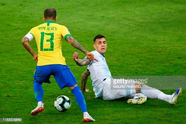 Brazil's Dani Alves drives the ball past Argentina's Leandro Paredes during their Copa America football tournament semifinal match at the Mineirao...