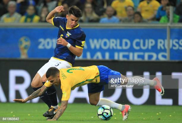 Brazil's Dani Alves falls next to Ecuador's Fernando Gaibor during their 2018 World Cup qualifier football match in Porto Alegre Brazil on August 31...