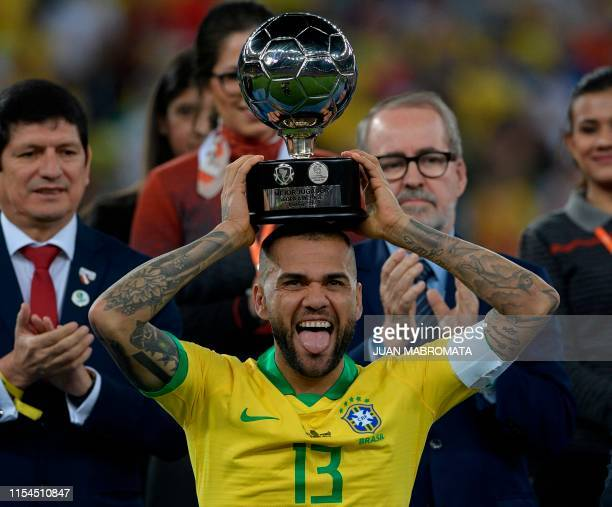 Brazil's Dani Alves poses with his trophy for Best Player of the Copa America after defeating Peru in the final match of the football tournament at...