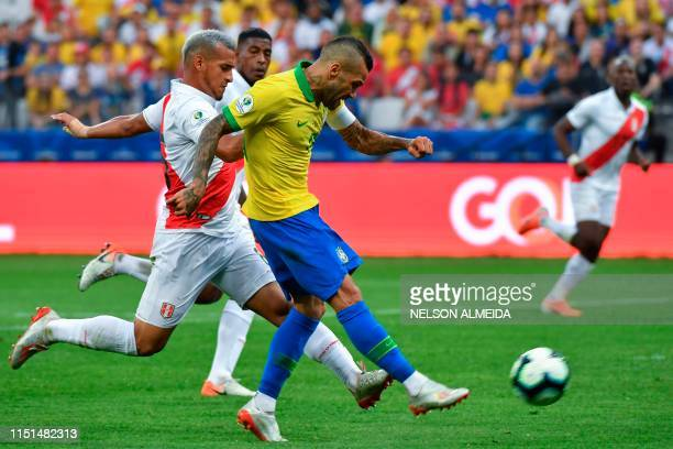 Brazil's Dani Alves strikes the ball past Peru's Miguel Trauco to score the team's fourth goal during their Copa America football tournament group...