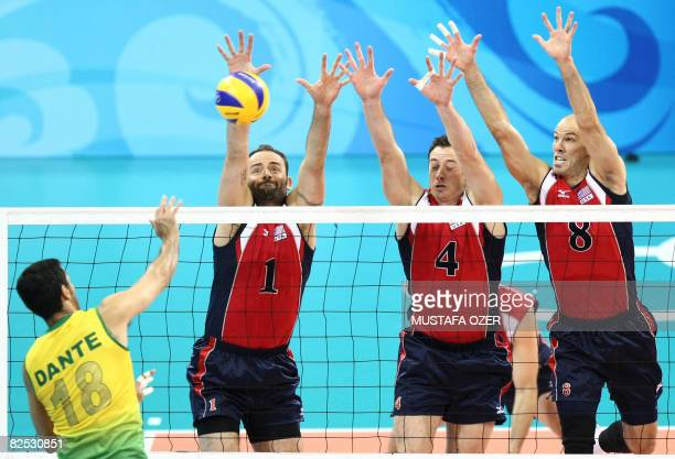 Brazil's Dante Amaral spikes the ball as US players Lloy Ball David Lee and William Priddy attempt to block during the men's volleyball gold medal...