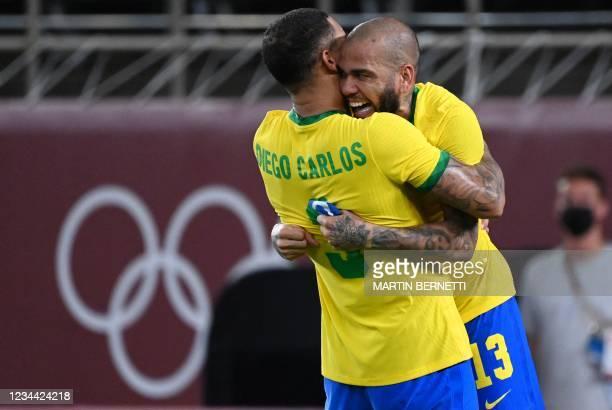 Brazil's defender Dani Alves and Brazil's defender Diego Carlos celebrate winning the Tokyo 2020 Olympic Games men's semi-final football match...