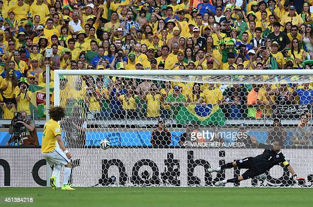 Brazil's defender David Luiz scores during the penalty shootout after the extra time in the round of 16 football match between Brazil and Chile at...